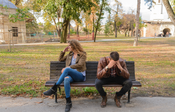 woman-and-man-sitting-on-brown-wooden-bench-984949